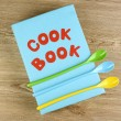 Cookbook and kitchenware on wooden background — Stock Photo #12089702