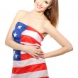 Beautiful young woman wrapped in American flag isolated on white — Stock Photo #12089725