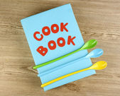 Cookbook and kitchenware on wooden background — Stockfoto
