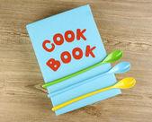 Libro de cocina y utensilios de cocina sobre fondo de madera — Foto de Stock