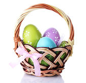 Basket with Easter eggs isolated on white — Stock Photo