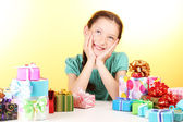 Little girl with gifts on yellow background — Stock Photo