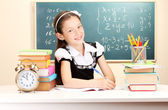 Little schoolchild in classroom write in notebook — Stock Photo