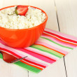 Cottage cheese with strawberry in orange bowl and fork on colorful napkin on white wooden table close-up — Stock Photo #12090130