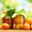 Canned apricots in a jars and sweet apricots on wooden table on green background — Stock Photo #12090216