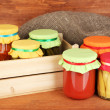 Jars with canned vegetables on wooden background close-up - Stock Photo