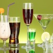 Variety of alcoholic drinks on green background — Stock Photo #12090336