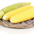 Fresh corn cobs on wicker mat isolated on white - Stock Photo