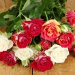 Bouquet of beautiful roses on wooden background close-up - Stock Photo
