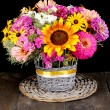 Beautiful bouquet of bright flowers on  wooden table on black background - Stock Photo