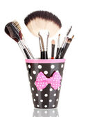 Makeup brushes in a black polka-dot cup isolated on white — Stock Photo