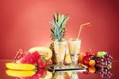 Melk schudt met fruit op rode achtergrond close-up — Stockfoto