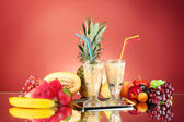 Milk shakes with fruit on red background close-up — Photo