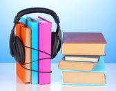 Kopfhörer auf bücher auf blauem hintergrund — Stockfoto