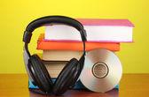 Kopfhörer auf bücher auf holztisch auf gelbem grund — Stockfoto