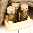 Glass jars with tinned capers in sack on white wooden background — Stock Photo