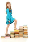 Liten flicka med en böcker isolerad på vit — Stockfoto