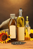 Oil in bottles, sunflowers and seeds, on wooden table on brown background — Stock Photo