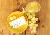 Cheese with mold and grapes on the plate on wooden background close-up — Stock Photo