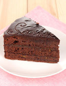 Chocolate sacher cake on wooden table — Stock Photo