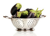 Fresh eggplants in colander isolated on white — Stock Photo