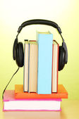 Headphones on books on wooden table on green background — Stock Photo