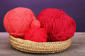 Red knittings yarns in basket on wooden table on purple background — Stock Photo