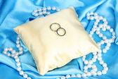 обручальные кольца на атласной подушече на фоне голубой ткани — Стоковое фото