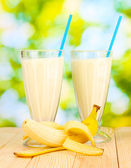 Banana milk shakes on wooden table on bright background — Stock Photo