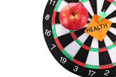 Darts with a sticker symbolizing health close-up on white background — Stock Photo