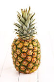 Pineapple on white wooden table — Stock Photo
