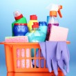 Basket with cleaning items on blue background — Stock Photo #12131121