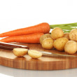 Young potatoes and carrots on a cutting board with knife isolated on white - Stock Photo