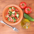 Fresh salad with tomatoes and cucumbers on wooden background — Stock Photo #12131689