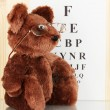 Royalty-Free Stock Photo: Teddy bear with glasses on eyesight test chart background close-up