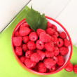 Fresh raspberries in bowl on white wooden background close-up - Stock Photo