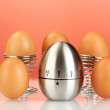 Egg timer and eggs on red background — Stock Photo
