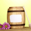 Stock Photo: Sweet honey in barrel with drizzler on wooden table on green background