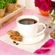 Cup of coffee, cookies, orange and flowers on table in cafe — Stock Photo #12137677