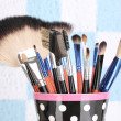 Makeup brushes in a black polka-dot cup on colorful background close-up - Stock Photo