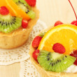 Sweet cake with fruits on wooden table — Stock Photo