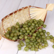 Green gooseberry in basket on wooden background - Stockfoto
