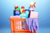 Basket with cleaning items on blue background — Stock Photo