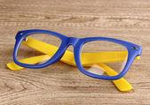 木制背景上美丽的颜色眼镜 — 图库照片