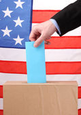 Hand with voting ballot and box on Flag of USA — Stock Photo