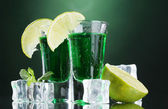 Two glasses of absinthe, lime and ice on green background — Stock Photo