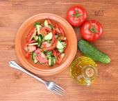 Fresh salad with tomatoes and cucumbers on wooden background — Stock Photo