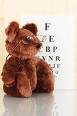 Teddy bear with glasses on eyesight test chart background close-up — Stock Photo