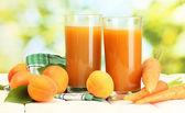 очки морковно-абрикосовый сок на белый деревянный стол на зеленом фоне — Стоковое фото