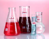 Test-tubes with various acids and chemicals on pink background — 图库照片